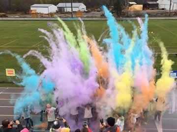 Puffs of colorful powder shooting upwards from the track